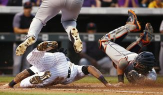 Colorado Rockies' Ian Desmond, left, is tagged out at home plate by Detroit Tigers catcher James McCann during the second inning of a baseball game Tuesday, Aug. 29, 2017, in Denver. (AP Photo/Jack Dempsey)