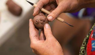 In an Aug. 8, 2017 photo, Anne Marie Horn sculpts a face during the Healing Through Art event at Art 321 in Casper, Wyoming. (Josh Galemore, Casper Star-Tribune via AP)