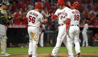 Los Angeles Angels' C.J. Cron, second from right, is congratulated by Kole Calhoun (56) and Luis Valbuena, right, after hitting a three-run home run, as Oakland Athletics catcher Bruce Maxwell waits during the first inning of a baseball game, Tuesday, Aug. 29, 2017, in Anaheim, Calif. (AP Photo/Mark J. Terrill)