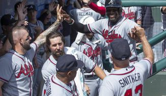 Atlanta Braves' Brandon Phillips, top right, celebrates scoring with teammates on a home run by Freddie Freeman during the first inning of the first baseball game of a doubleheader against the Philadelphia Phillies, Wednesday, Aug. 30, 2017, in Philadelphia. (AP Photo/Chris Szagola)