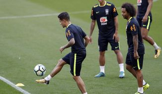 Brazil's Philippe Coutinho, left, practices as teammates Firmino, center, and Marcelo look on during a training session in Porto Alegre, Brazil, Tuesday, Aug. 29, 2017. Brazil will face Ecuador in a 2018 World Cup qualifying soccer match on Aug. 31. (AP Photo/Andre Penner)