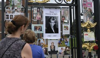 Tourists look at tributes and memorabilia for the late Diana, Princess of Wales outside Kensington Palace in London, Tuesday, Aug. 29, 2017. The tributes are placed on one of the ornamental gates at the palace ahead of the 20th anniversary of Princess Diana's death, in a car crash in Paris Aug. 31, 1997. (AP Photo/Alastair Grant)
