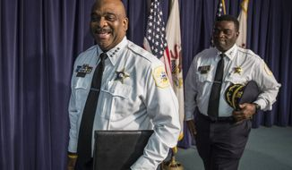 In this Tuesday, Aug. 29, 2017 photo, Chicago Police Superintendent Eddie Johnson, left,  smiles as he leaves a press conference in Chicago, acknowledging a reporter who wished him well for his kidney transplant surgery scheduled for Wednesday. Johnson disclosed in January after suffering a public dizzy spell that he has battled for decades a potentially life-threatening inflammation of his kidneys and was on a waiting list for a kidney transplant. Johnson's 25-year-old son is donating one of his kidneys to his father. (Rich Hein/Sun Times via AP)