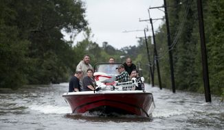 Residents of a neighborhood in northwest Beaumont are rescued by boat in Beaumont, Texas, after Hurricane Harvey on Wednesday Aug. 30, 2017. (Jay Janner/Austin American-Statesman via AP)