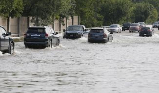 "Vehicles drive through floodwaters in the aftermath of Harvey, in Friendswood, Texas on Wednesday, Aug. 30, 2017.  Gov. Greg Abbott said Wednesday that ""the worst is not over"" for southeastern Texas as widespread flooding continues.  (Kevin M. Cox/The Galveston County Daily News via AP)"