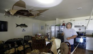 Louis Sirianni uses a flashlight to check damages cased to his home by the effects of Harvey, Tuesday, Aug. 29, 2017, in Rockport, Texas. (AP Photo/Eric Gay)