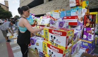Volunteer Elizabeth Haley organizes boxes of infant diapers donated for hurricane Harvey victims at a North Dallas donation drop off location, Tuesday, Aug. 29, 2017. (AP Photo/Tony Gutierrez)