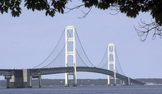 FILE - In this July 19, 2002 file photo, the Mackinac Bridge that spans the Straits of Mackinac is shown from Mackinaw City, Mich. The company that operates twin oil pipelines beneath the waterway that links Lake Huron and Lake Michigan says it has discovered a number of gaps in a layer of protective enamel coating on one of the pipes. Enbridge Inc. said Wednesday, Aug. 30, 2017, the gaps were noticed during a recent inspection. Spokesman Ryan Duffy says they're small and apparently were formed when workers installed steel anchors to support the pipelines in the Straits of Mackinac. (AP Photo/Carlos Osorio, File)
