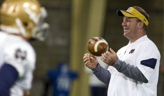 FILE - In this March 22, 2017 file photo, Notre Dame defensive coordinator Mike Elko runs drills during NCAA college football practice in South Bend, Ind. Brian Kelly kind of shrugged his shoulders and laughed when he was asked to list the most necessary areas of defensive improvement if this is to become a turnaround season for Notre Dame. Kelly hopes that hiring Mike Elko away from Wake Forest as his new defensive coordinator will be the catalyst to that change in style, scheme and success. (Becky Malewitz/South Bend Tribune via AP, File)