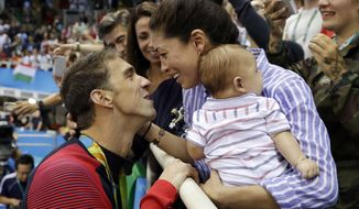FILE - In this Aug. 9, 2016, file photo, United States' swimmer Michael Phelps celebrates winning his gold medal in the men's 200-meter butterfly with his wife Nicole and baby Boomer during the swimming competitions at the 2016 Summer Olympics, in Rio de Janeiro, Brazil. Phelps announced on Instagram Aug. 29, 2017, that Nicole is pregnant. (AP Photo/Matt Slocum, File)