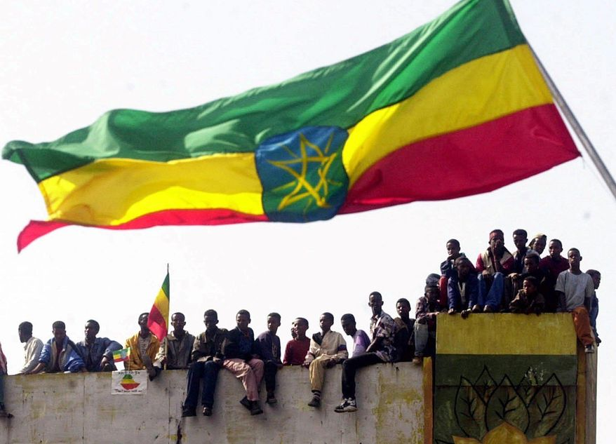 FILE - In this May, 28, 2000 file photo, Ethiopians sit under an Ethiopian flag as they watch a parade in Addis Ababa, Ethiopia, marking the Ethiopian army's latest victories in the Ethiopia-Eritrea war. Qatar and the Arab nations now allied against it have made inroads in the Horn of Africa in recent years by establishing military bases now being used in the Yemen war, as well as managing ports and showering friendly nations with foreign aid. The Qatar diplomatic crisis now is shaking those East African nations amid an increasingly fierce competition for influence. (AP Photo/Pier Paolo Cito, File)