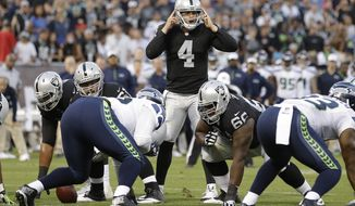 FILE - In this Aug. 28, 2014, file photo, Oakland Raiders quarterback Derek Carr (4) calls out at the line of scrimmage against the Seattle Seahawks during an NFL preseason football game in Oakland, Calif. Carr will spend Thursday night's preseason finale for the Raiders on the sideline, too important to risk an injury. But don't tell Carr these games are meaningless. It was his performance in the final exhibition game as a second-round draft pick three years ago that solidified his place as the starting quarterback in Oakland. (AP Photo/Ben Margot, File)