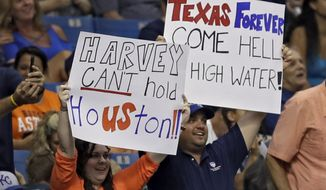 Fans hold up signs as a show of support for the city of Houston during the sixth inning of a baseball game between the Houston Astros and the Texas Rangers Wednesday, Aug. 30, 2017, in St. Petersburg, Fla. The Astros moved their three-game home series against the Rangers to St. Petersburg after being displaced by Hurricane Harvey. (AP Photo/Chris O'Meara)