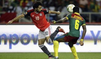 FILE- In this Sunday, Feb. 5, 2017 file photo, Egypt's Mohamed Salah, left, controls the ball in front of Cameroon's Ambroise Oyongo during the African Cup of Nations final soccer match between Egypt and Cameroon at the Stade de l'Amitie, in Libreville, Gabon. Egypt, the most successful team in Africa but a regular underachiever in World Cup qualifying, is in control of Group E. (AP Photo/Sunday Alamba, File)