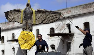 FILE- In this Feb. 10, 2006 file photo, workers salvage the eagle from the World War II German pocket battleship Admiral Graf Spee, in Montevideo, Uruguay. Controversy has swirled around the eagle ever since it was recovered and now a battle has broken out over its fate. Suggestions have ranged from exhibiting or auctioning the Third Reich symbol, to keeping it hidden or even destroying it. (AP Photo/Marcelo Hernandez, File)