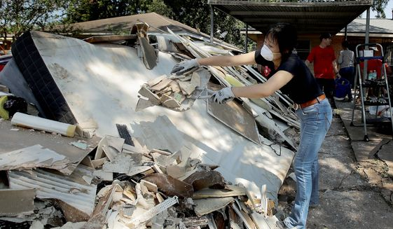 Lucy Liu helped her co-worker Tianna Oliver clean out her flood-damaged house on Thursday. Government agencies also have kicked into high gear as the Houston region begins to recover from Hurricane Harvey. (Associated Press)