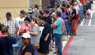 As people wait in line for necessities in short supply thanks to Hurricane Harvey, top government officials are keeping an eye on shop owners to see how they handle price gouging. (Associated Press)