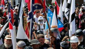 In this Saturday, Aug. 12, 2017, file photo, white nationalist demonstrators walk into the entrance of Lee Park surrounded by counter demonstrators in Charlottesville, Va. (AP Photo/Steve Helber) ** FILE **