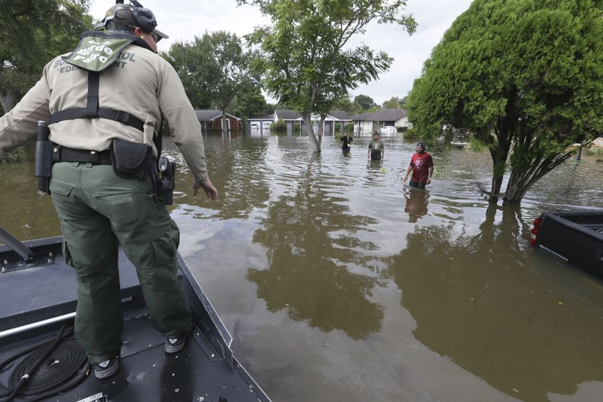 U.S. Border Patrol Agent Steven Blackburn, left, checks if people wading in water need help during a search a rescue operation in a neighborhood inundated by floodwaters from Tropical Storm Harvey in Houston, Texas, Wednesday, Aug. 30, 2017. (AP Photo/LM Otero)