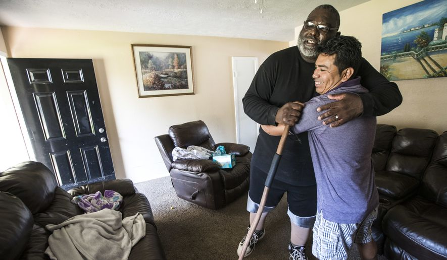 Boyd Jones, left, embraces his neighbor, Manuel Rosales as they meet in Rosales' home after being flooded in the aftermath of Tropical Storm Harvey in the Verde Forest subdivision of Houston on Thursday, Aug. 31, 2017. (Brett Coomer/Houston Chronicle via AP)
