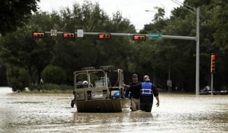 Houston police officers patrol among floodwaters from Tropical Storm Harvey Wednesday, Aug. 30, 2017, in Kingwood, Texas. (AP Photo/Gregory Bull)