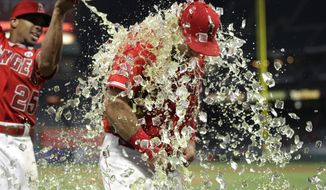 Los Angeles Angels' Cliff Pennington is doused with liquid by Ben Revere following the team's 10-8 win against the Oakland Athletics in a baseball game, Wednesday, Aug. 30, 2017, in Anaheim, Calif. Pennington hit his first career grand slam. (AP Photo/Jae C. Hong)