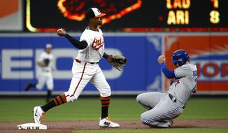 Baltimore Orioles shortstop Tim Beckham, left, throws to first base for a double play after forcing out Toronto Blue Jays' Josh Donaldson, right, at second on Kendrys Morales' ground ball in the first inning of a baseball game in Baltimore, Thursday, Aug. 31, 2017. (AP Photo/Patrick Semansky)