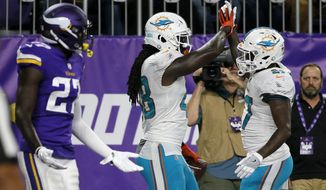 Miami Dolphins tight end MarQueis Gray, center, celebrates with teammate Storm Johnson, right, after catching a 6-yard touchdown pass during the first half of an NFL preseason football game against the Minnesota Vikings, Thursday, Aug. 31, 2017, in Minneapolis. Vikings safety Jayron Kearse is at left. (AP Photo/Bruce Kluckhohn)