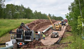 In this July 25, 2017, photo provided by Wisconsin Public Radio, crews begin work on the Wisconsin segment of Enbridge Energy's Line 3 near Superior, Wis. Six activists were arrested Tuesday, Aug. 29, for obstructing the work, and more protests are planned this weekend. (Elizabeth McMahon/Wisconsin Public Radio via AP)