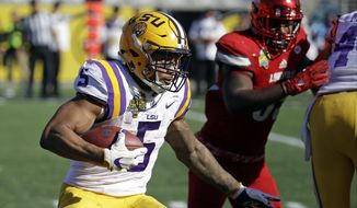 FILE - In this Dec. 31, 2016, file photo, LSU running back Derrius Guice (5) runs against Louisville during the second half of the Citrus Bowl NCAA football game in Orlando, Fla.  LSU's old offense suited Derrius Guice fine when he set an LSU single-game rushing record with one of the most dominant performances in all of college football last season. Still, he's had to accept a new scheme under a new coordinator, and have faith that it'll all work out for the 13th-ranked Tigers. (AP Photo/John Raoux, File)