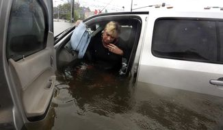 FILE - In this Monday, Aug. 28, 2017, file photo, Rhonda Worthington talks on her cellphone with a 911 dispatcher as she gets out of her car after her vehicle become stalled in rising floodwaters from Harvey in Houston. Cellphone networks are largely functional in the Texas and Louisiana regions hit by Harvey, as cellphone companies brought in supplemental equipment and backup power and turned to drones to diagnose problems. (AP Photo/LM Otero, File)