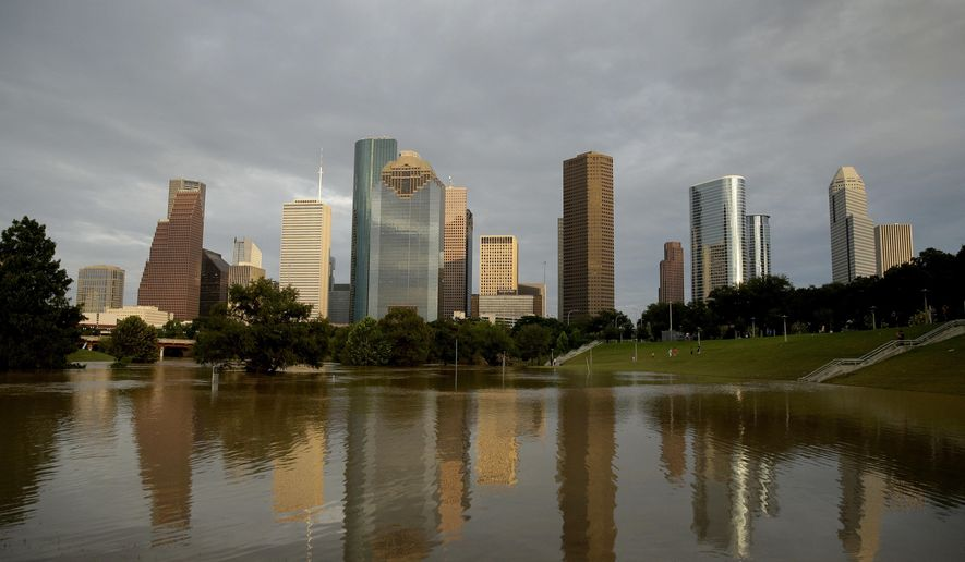 Dowtown Houston is reflected in flooded Buffalo Bayou, Wednesday, Aug. 30, 2017, as the city continues to recover from record flooding caused by Tropical Storm Harvey. (AP Photo/Charlie Riedel)