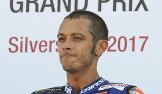 FILE - In this Aug. 27, 2017 file photo, Italy's Valentino Rossi of Movistar Yamaha looks on after finishing third in the Moto GP race at the British Grand Prix at Silverstone, England. Six-time MotoGP champion Rossi has reportedly broken his right leg in a training accident in Italy. According to Italian sports daily Gazzetta dello Sport, Rossi fell during enduro training and fractured his tibia and fibula. (AP Photo/Rui Vieira)