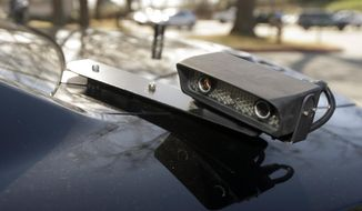 FILE- In this Jan. 16, 2013, file photo, a camera is mounted near the rear window of a police car in Little Rock, Ark. The device is part of a system that scans traffic on the streets, relaying the data it collects to a computer for sifting. It would violate people's privacy to publicly release raw data collected by automated license plate readers that police use to determine whether vehicles are linked to crime, but there may be ways to make the information anonymous that would require it to be disclosed, the California Supreme Court said Thursday, Aug. 31, 2017. (AP Photo/Danny Johnston, File)