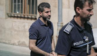 Tavan Resit, a Turkish businessman the United States wants to extradite on suspicion of supporting Iran's military procurement plan, walks handcuffed after asking a Romanian court to free him from arrest, in Bucharest, Romania, Thursday, Aug. 31, 2017. Resit was arrested on June 8 in Romania, where he had traveled to meet with U.S. officials. (AP Photo/Vadim Ghirda)