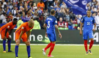 France's Kylian Mbappe, right, and France's Layvin Kurzawa reacts while Netherlands' Arjen Robben, 2nd left, looks on at the end of the World Cup Group A qualifying soccer match between France and The Netherlands at the Stade de France stadium in Saint-Denis, outside Paris, Thursday, Aug.31, 2017. (AP Photo/Francois Mori)