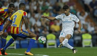 FILE- In this Sunday, Aug. 27, 2017 file photo, Real Madrid's Marco Asensio, right, scores the opening goal past Valencia's Ruben Vezo during a Spanish La Liga soccer match between Real Madrid and Valencia at the Santiago Bernabeu stadium in Madrid. Spain is hoping that it has found its next great talent. Marco Asensio has had a breakout start to the season with Real Madrid. (AP Photo/Francisco Seco)