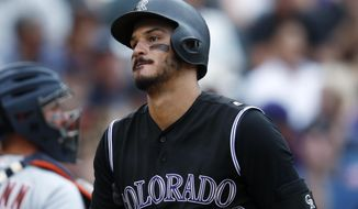 Colorado Rockies' Nolan Arenado, front, reacts after striking out on a pitch from Detroit Tigers reliever Alex Wilson to end the bottom of the eighth inning of a baseball game Wednesday, Aug. 30, 2017, in Denver. The Tigers won 6-2. (AP Photo/David Zalubowski)