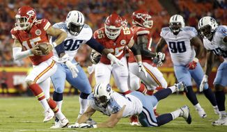 Kansas City Chiefs quarterback Patrick Mahomes (15) runs past a tackle-attempt by Tennessee Titans defensive lineman Karl Klug (97) during the first half of an NFL preseason football game in Kansas City, Mo., Thursday, Aug. 31, 2017. (AP Photo/Colin E. Braley)