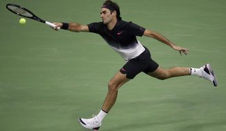 Roger Federer, of Switzerland, returns a shot to Frances Tiafoe, of the United States, during the U.S. Open tennis tournament, Tuesday, Aug. 29, 2017, in New York. (AP Photo/Julio Cortez)