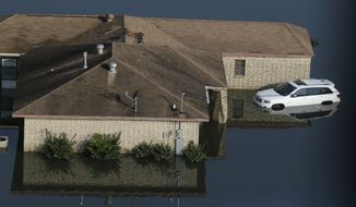 In this aerial photo, a flooded home with a hole cut in the roof sits in floodwaters caused Tropical Storm Harvey in Port Arthur, Texas, Friday, Sept. 1, 2017.  Port Arthur's major roads were swamped by rising waters brought by Harvey(AP Photo/LM Otero)