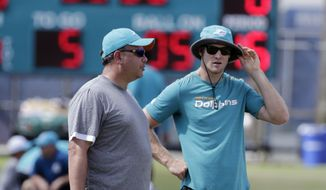 FILE - In this Aug. 7, 2017, file photo, Miami Dolphins quarterback Ryan Tannehill, right, watches practice during an NFL football training camp in Davie, Fla. When Tannehill took a misstep on a run and injured his knee, coach Adam Gase turned to Jay Cutler, with whom he has a successful history. (AP Photo/Lynne Sladky, File) **FILE**