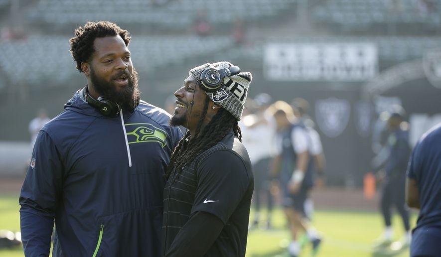 Seattle Seahawks defensive end Michael Bennett, left, talks with Oakland Raiders running back Marshawn Lynch before an NFL preseason football game between the Raiders and the Seahawks in Oakland, Calif., Thursday, Aug. 31, 2017. (AP Photo/Eric Risberg)