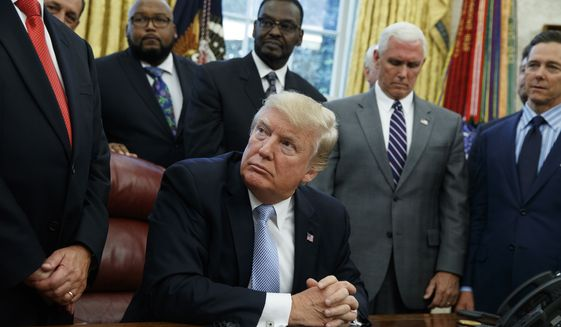 President Donald Trump listens as faith leaders speak after he signed a proclamation for a national day of prayer to occur on Sunday, Sept. 3, 2017, in the Oval Office of the White House, Friday, Sept. 1, 2017, in Washington. (AP Photo/Evan Vucci)