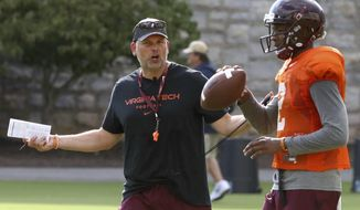 FILE - In this Aug. 3, 2017, file photo, Virginia Tech head coach Justin Fuente instructs quarterback Hendon Hooker (2) during an NCAA college football practice in Blacksburg, Va. No. 21 Virginia Tech takes on No. 22 West Virginia on Saturday, Sept. 2, in Landover, Md.(Matt Gentry/The Roanoke Times via AP, File)