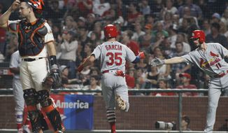 St. Louis Cardinals' Greg Garcia (35) is greeted at the plate by Paul DeJong, right, after scoring on a Tommy Pham single during the seventh inning of a baseball game against the San Francisco Giants, Thursday, Aug. 31, 2017, in San Francisco. Giants' Buster Posey is at left. (AP Photo/George Nikitin)