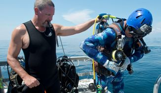 "ADVANCE FOR SUNDAY, SEPT. 3 - This undated file photo taken in 2014, Kerry Freeland, left, helps Dave Mucci as he puts on his dive gear before diving to the S.S. San Pablo, also known as the ""Russian Freighter,"" in the Gulf of Mexico. (Tony Giberson/Pensacola News Journal via AP)"