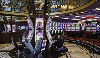 People play slot machines in a newly opened expansion at the Golden Gate hotel-casino, Friday, Sept. 1, 2017, in Las Vegas. The casino, a fixture on Fremont Street for more than 100 years, reopens after an expansion project that reflects the resurgence under way in downtown Las Vegas. (AP Photo/John Locher)