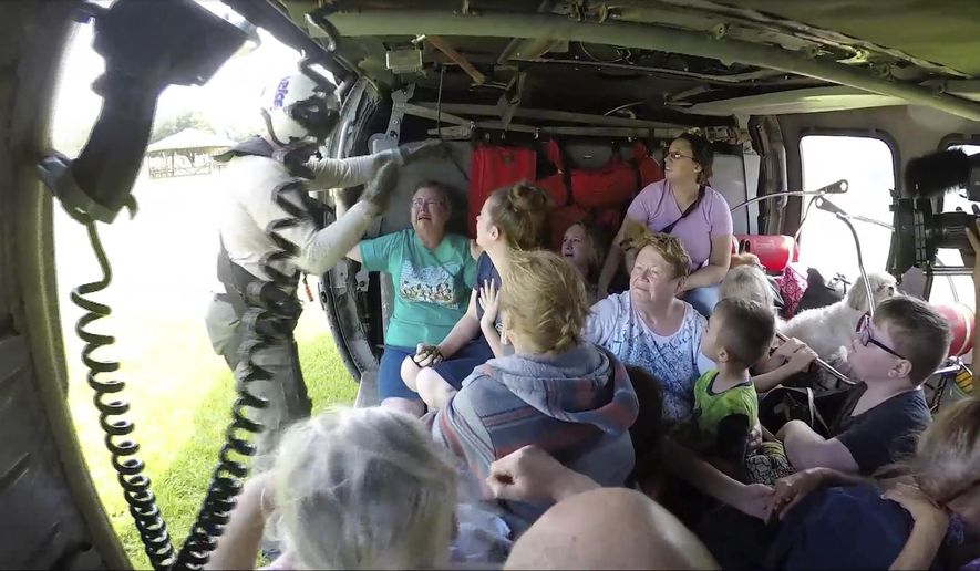 This still image taken from video provided by the U.S. Navy shows sailors from Helicopter Sea Combat Squadron (HSC) 28 rescuing 14 people and four dogs, at Pine Forrest Elementary School, in Vidor, Texas on Thursday, Aug. 31, 2017.  The shelter that required evacuation after flood waters from Hurricane Harvey reached its grounds.  (U.S. Navy via AP)