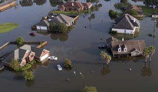 In this aerial photo, homes sit in floodwaters caused Tropical Storm Harvey in Port Arthur, Texas, Friday, Sept. 1, 2017.  Port Arthur's major roads were swamped by rising waters brought by Harvey(AP Photo/LM Otero)